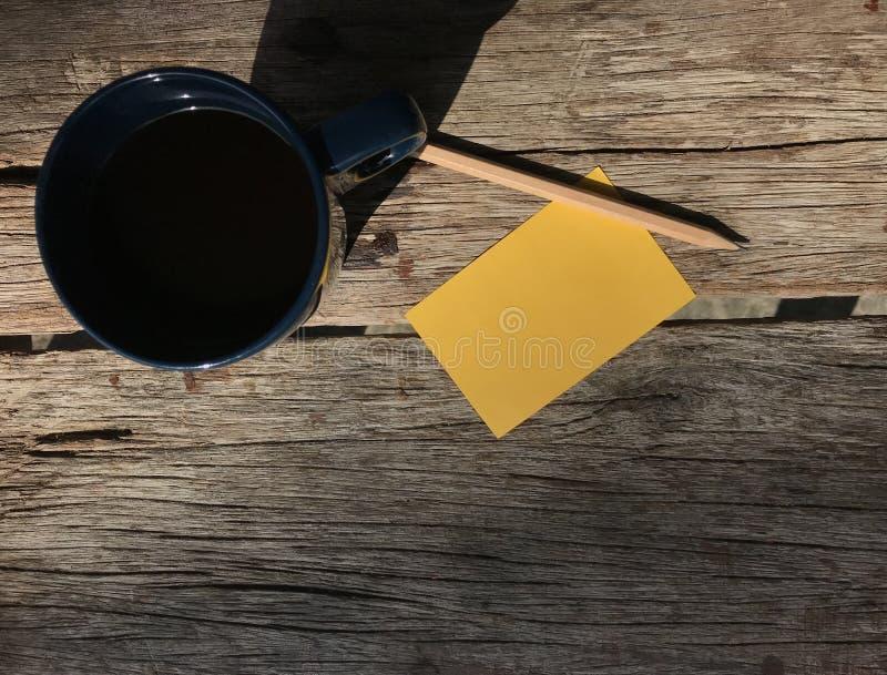 Τοπ άποψη του μπλε φλυτζανιού του καυτού καφέ, του κίτρινου σημειωματάριου και του ξύλινου μολυβιού στοκ φωτογραφία με δικαίωμα ελεύθερης χρήσης