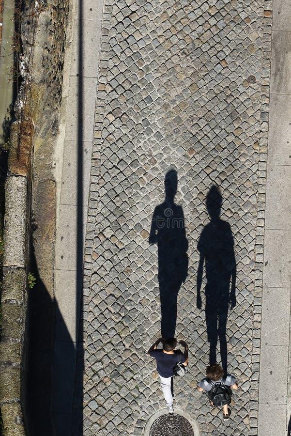 Τοπ άποψη του νέου ζευγαριού τουριστών στην οδό με τις σκιές στοκ φωτογραφίες