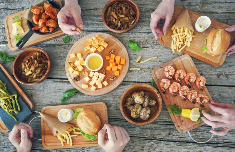 Τοπ άποψη του πίνακα με τα τρόφιμα και το πρόχειρο φαγητό στοκ εικόνες
