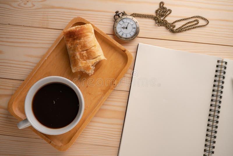 Τοπ άποψη του παλαιού χρυσού ρολογιού τσεπών που τοποθετείται στην πλευρά του ξύλινου δίσκου με μια άσπρη κούπα καφέ και την πίτα στοκ εικόνα με δικαίωμα ελεύθερης χρήσης