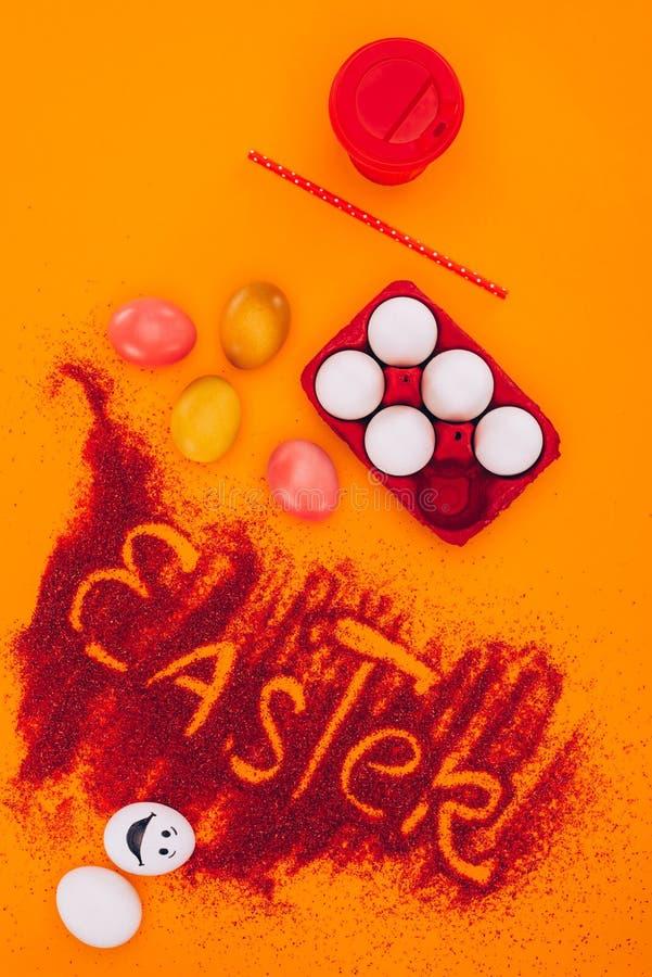 Τοπ άποψη του σημαδιού Πάσχας φιαγμένη από κόκκινη άμμο με τα αυγά και τον καφέ κοτόπουλου στοκ εικόνες