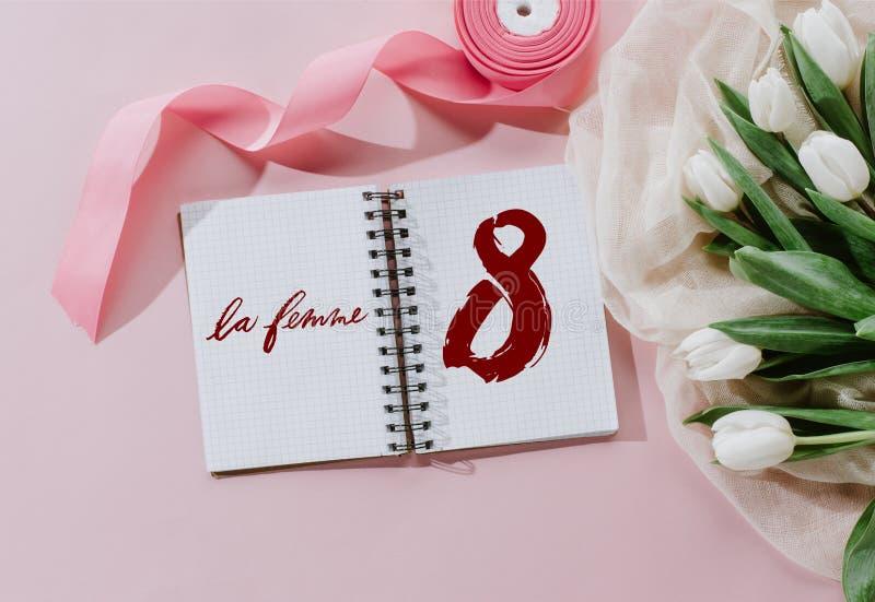 τοπ άποψη του σημαδιού LE FEMME στη ρόδινη κορδέλλα σημειωματάριων και των άσπρων τουλιπών για διεθνή απεικόνιση αποθεμάτων