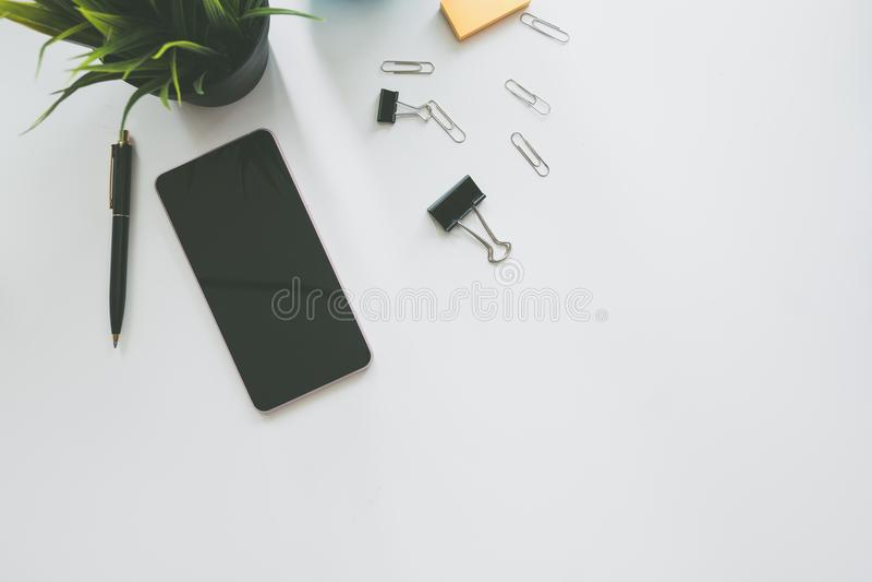 Τοπ άποψη του σύγχρονου πίνακα γραφείων γραφείων διαστήματος εργασίας με το έξυπνο τηλέφωνο στοκ φωτογραφία