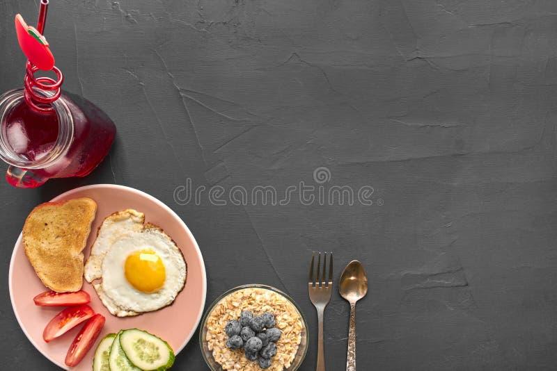 Τοπ άποψη του υγιούς και εύγευστου προγεύματος σε ένα μαύρο υπόβαθρο με το copyspace στοκ φωτογραφία