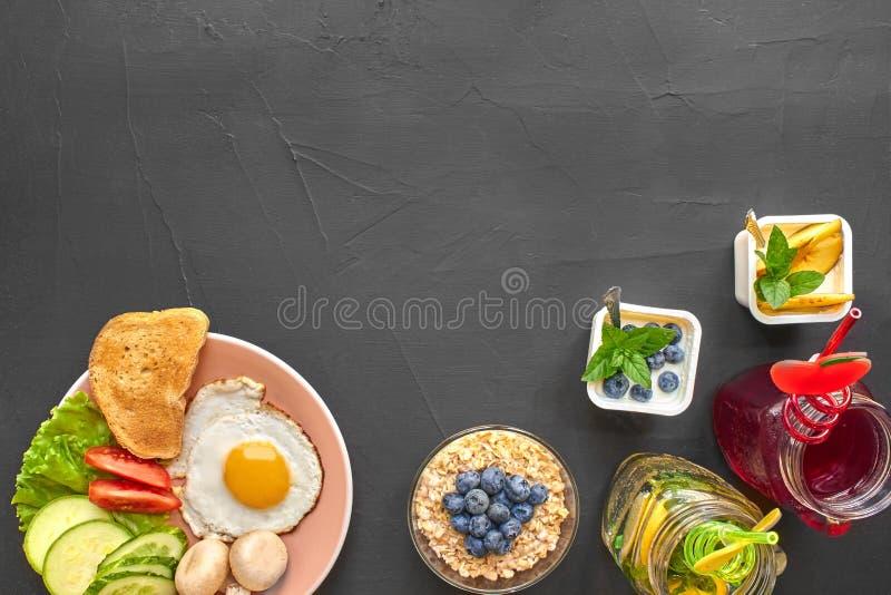 Τοπ άποψη του υγιούς και εύγευστου προγεύματος σε ένα μαύρο υπόβαθρο με το copyspace στοκ εικόνα