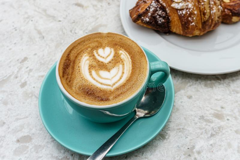 Τοπ άποψη του φλιτζανιού του καφέ με τον αφρό και croissant στον πίνακα στοκ φωτογραφίες με δικαίωμα ελεύθερης χρήσης