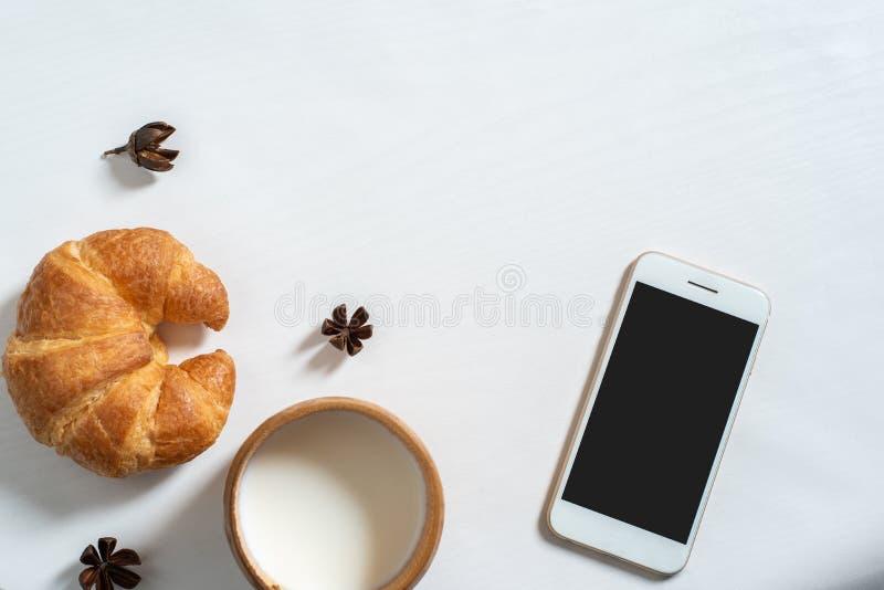 Τοπ άποψη του φλυτζανιού του γάλακτος, βιβλίο σημειώσεων, croissant στον ξύλινο πίνακα στοκ εικόνες με δικαίωμα ελεύθερης χρήσης