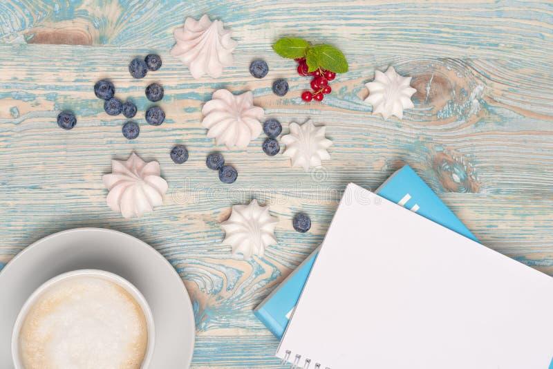 Τοπ άποψη του φλυτζανιού καφέ με τη μαρέγκα, τα βακκίνια και την κόκκινη σταφίδα κοντά στο ανοικτό σημειωματάριο στο ξύλινο γραφε στοκ φωτογραφία
