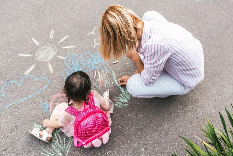 Τοπ άποψη του χαριτωμένου μικρού κοριτσιού και του σχεδίου μητέρων της με τις ζωηρόχρωμες κιμωλίες στο πεζοδρόμιο Καυκάσιο ξανθό  στοκ φωτογραφίες με δικαίωμα ελεύθερης χρήσης