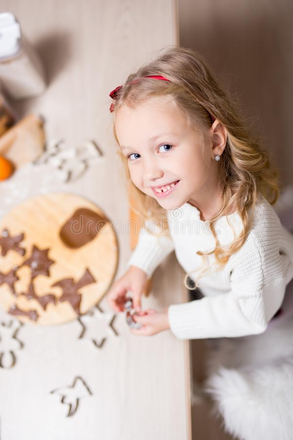 Τοπ άποψη του χαριτωμένου μικρού κοριτσιού που κατασκευάζει τα μπισκότα Χριστουγέννων στην κουζίνα στοκ εικόνες