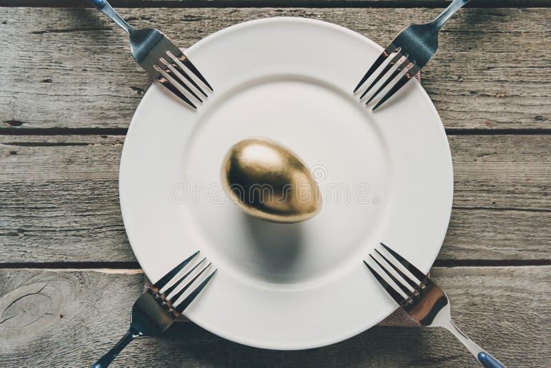 Τοπ άποψη του χρυσού αυγού Πάσχας στο άσπρο πιάτο και των δικράνων στον ξύλινο πίνακα στοκ εικόνες
