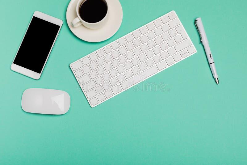Τοπ άποψη του χώρου εργασίας γραφείων γραφείων με το smartphone, το πληκτρολόγιο, τον καφέ και το ποντίκι στο μπλε υπόβαθρο με το στοκ φωτογραφία