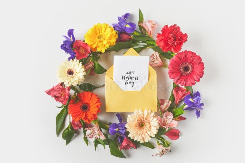 τοπ άποψη του όμορφου floral στεφανιού και της ευτυχούς ευχετήριας κάρτας ημέρας μητέρων στο φάκελο στο γκρι στοκ φωτογραφία με δικαίωμα ελεύθερης χρήσης