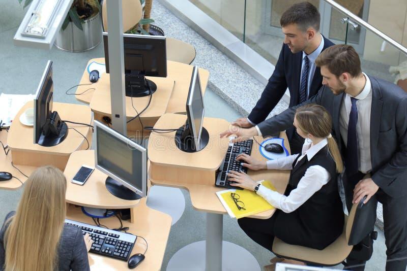Τοπ άποψη του 'brainstorming' επιχειρησιακών ομάδων καθμένος στον πίνακα γραφείων από κοινού στοκ εικόνες