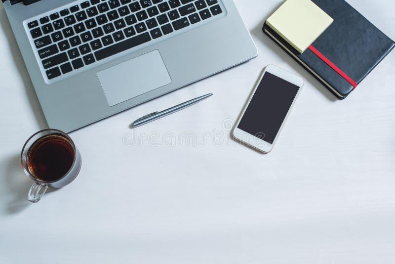Τοπ άποψη του lap-top, μαύρο σημειωματάριο, κινητό τηλέφωνο, μάνδρα, ένα φλυτζάνι του τσαγιού στοκ εικόνα
