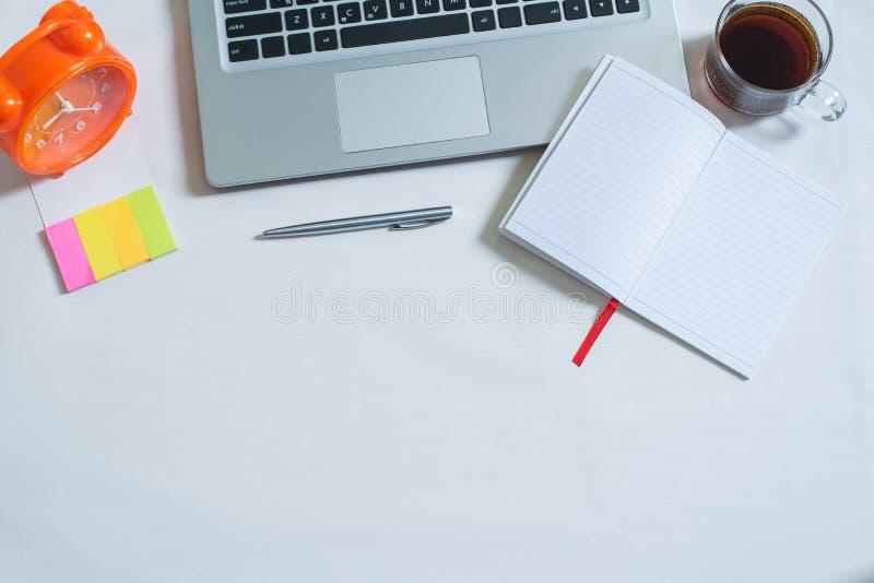 Τοπ άποψη του lap-top, φλυτζάνι του τσαγιού, ανοικτό σημειωματάριο, μάνδρα, ζωηρόχρωμη μίνι σημείωση εγγράφου, πορτοκαλί ρολόι στοκ φωτογραφία