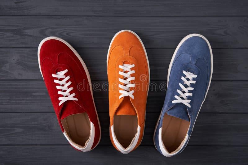 Τοπ άποψη τριών πάνινων παπουτσιών σουέτ στις γκρίζες ξύλινες σανίδες στοκ φωτογραφία με δικαίωμα ελεύθερης χρήσης
