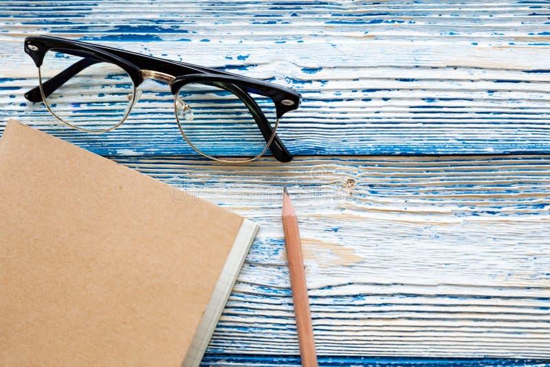 Τοπ άποψη των γυαλιών και του μολυβιού σημειωματάριων στον ανοικτό μπλε ξύλινο πίνακα στοκ εικόνες