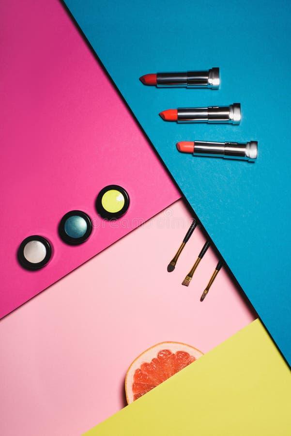 τοπ άποψη των διάφορων προμηθειών makeup με τη φέτα γκρέιπφρουτ στοκ φωτογραφία