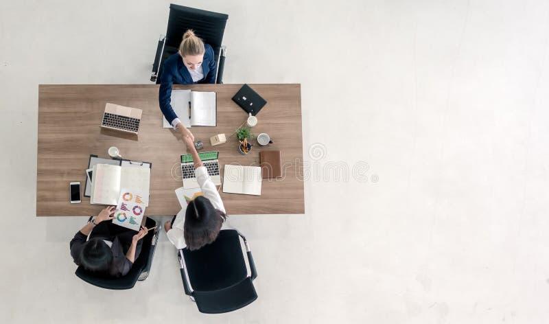 Τοπ άποψη των επιχειρηματιών που τινάζουν τα χέρια μετά από να σφραγίσει μια διαπραγμάτευση Υψηλή άποψη γωνίας της περιστασιακής  στοκ εικόνα με δικαίωμα ελεύθερης χρήσης
