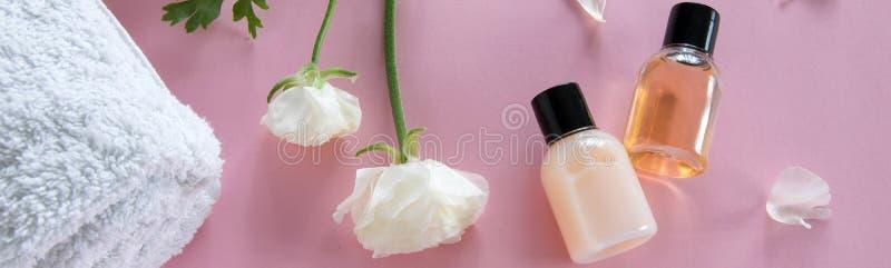 Τοπ άποψη των καλλυντικών προϊόντων και των λεπτών λουλουδιών στο ρόδινο υπόβαθρο Επεξεργασία ομορφιάς Wellness στοκ εικόνα με δικαίωμα ελεύθερης χρήσης