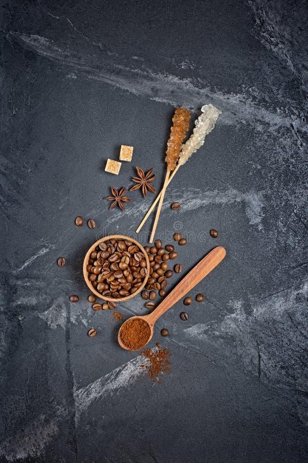 Τοπ άποψη των καφετιών ψημένων φασολιών καφέ στο ξύλινο ραβδί κρυστάλλου κύπελλων και ζάχαρης στοκ εικόνες