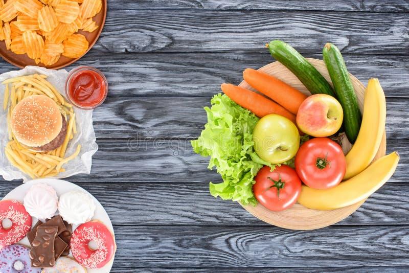 τοπ άποψη των νωπών καρπών με τα λαχανικά και των πιάτων με το άχρηστο φαγητό στον ξύλινο πίνακα στοκ φωτογραφίες