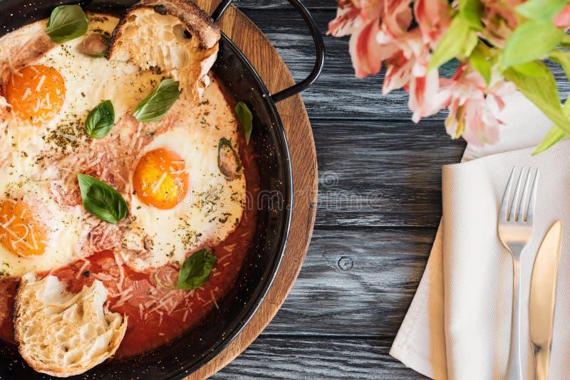 τοπ άποψη των νόστιμων ψημένων αυγών, του δικράνου με το μαχαίρι και των λουλουδιών στοκ εικόνα