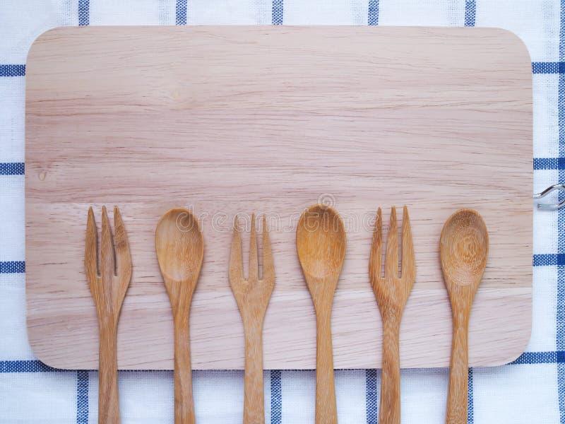 Τοπ άποψη των ξύλινων μαχαιροπήρουνων, του κουταλιού και του δικράνου στον τέμνοντα πίνακα στοκ φωτογραφία