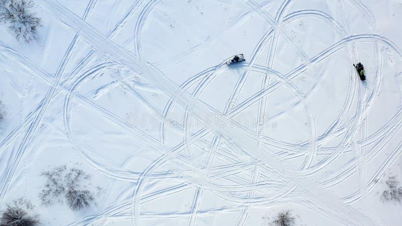 Τοπ άποψη των οχημάτων για το χιόνι οδήγησης footage Τοπ άποψη δύο οχημάτων για το χιόνι που οδηγούν στον κύκλο που αφήνει τα ίχν στοκ εικόνα με δικαίωμα ελεύθερης χρήσης