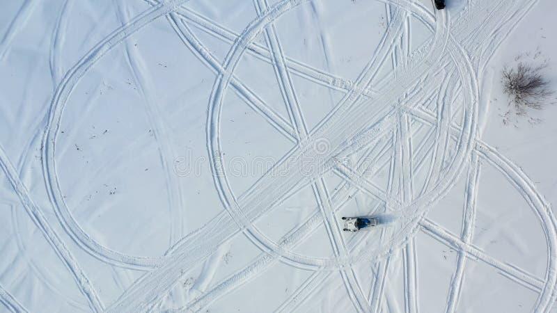 Τοπ άποψη των οχημάτων για το χιόνι οδήγησης footage Τοπ άποψη δύο οχημάτων για το χιόνι που οδηγούν στον κύκλο που αφήνει τα ίχν στοκ φωτογραφία με δικαίωμα ελεύθερης χρήσης