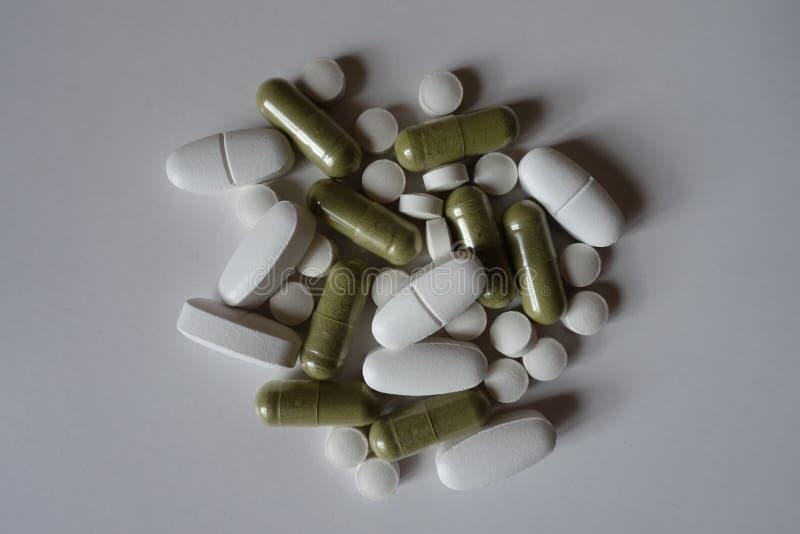 Τοπ άποψη των πράσινων moringa καψών, των άσπρων caplets ασβεστίου και των ταμπλετών βιταμίνη Κ στοκ φωτογραφίες με δικαίωμα ελεύθερης χρήσης