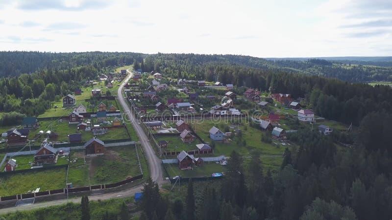 Τοπ άποψη των προαστιακών περιοχών με τα εξοχικά σπίτια στο δασικό συνδετήρα Ήρεμη και μέτρια ζωή στη δασική έκταση στοκ φωτογραφία