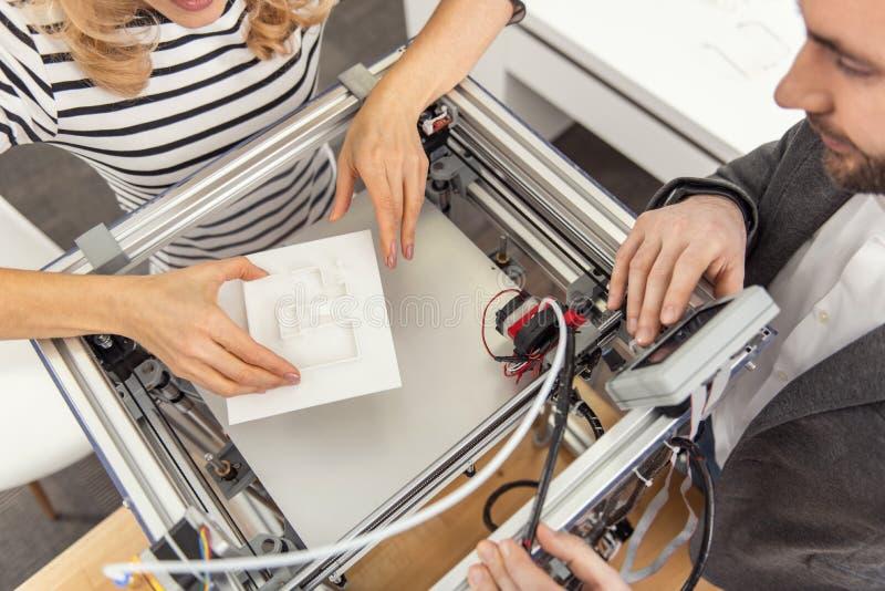 Τοπ άποψη των συναδέλφων που παρεμβάλλουν το μισό-γίνοντα πρότυπο στον τρισδιάστατο εκτυπωτή στοκ εικόνες