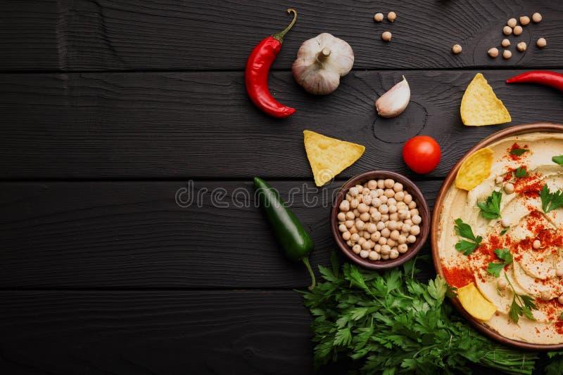 Τοπ άποψη των συστατικών hummus Κίτρινα hummus και τσιπ σε ένα ξύλινο υπόβαθρο Έννοια προετοιμασιών Hummus διάστημα αντιγράφων στοκ εικόνες με δικαίωμα ελεύθερης χρήσης