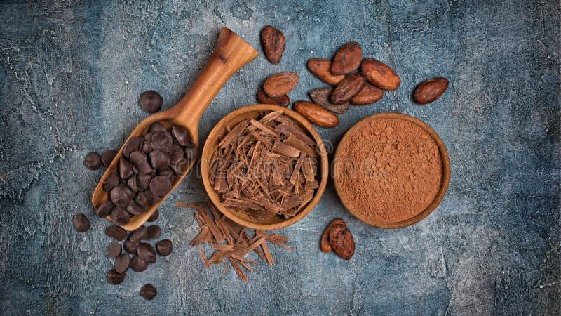 Τοπ άποψη των τσιπ σοκολάτας και των πτώσεων ή αλίπαστα με τα φασόλια κακάου και σκόνη για τη βιομηχανία ζαχαρωδών προϊόντων στοκ φωτογραφία με δικαίωμα ελεύθερης χρήσης