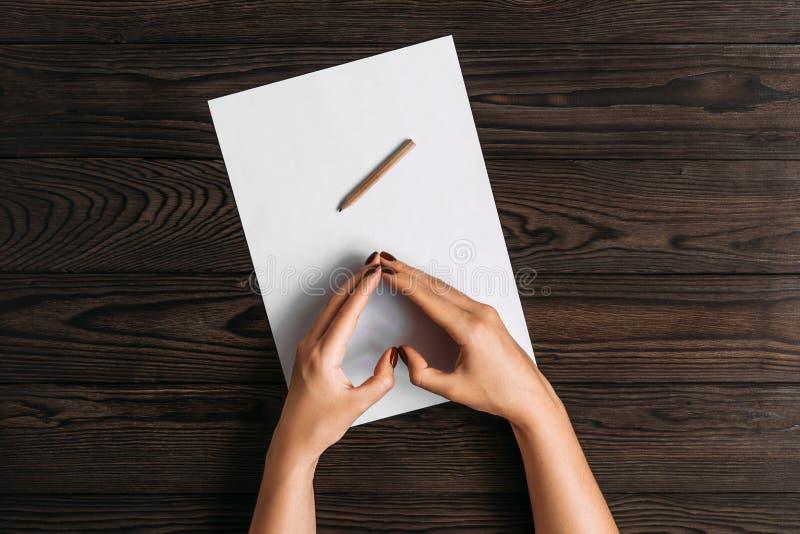 Τοπ άποψη των χεριών των γυναικών, έτοιμη να γράψει κάτι σε ένα κενό κομμάτι χαρτί που βρίσκεται σε έναν ξύλινο πίνακα Άσπρο κενό στοκ εικόνες