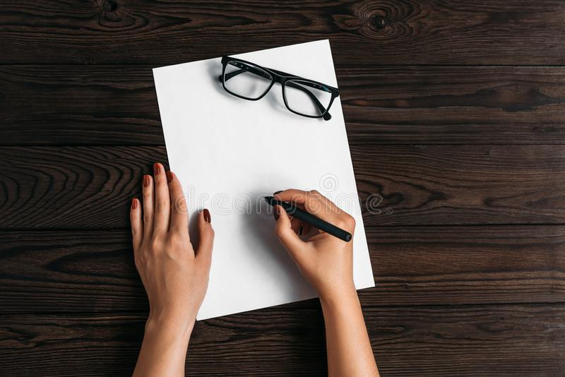 Τοπ άποψη των χεριών των γυναικών, έτοιμη να γράψει κάτι σε ένα κενό κομμάτι χαρτί που βρίσκεται σε έναν ξύλινο πίνακα Γράψτε μια στοκ εικόνα με δικαίωμα ελεύθερης χρήσης