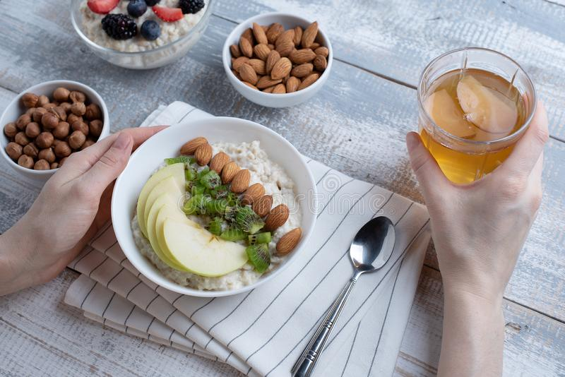 Τοπ άποψη των χεριών των γυναικών στο πρόγευμα, oatmeal με τα αμύγδαλα και τη Apple, καρύδια, μούρα, compote στοκ φωτογραφία