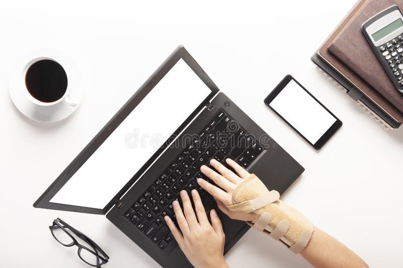 Τοπ άποψη των χεριών με τον πόνο καρπών από τη χρησιμοποίηση του υπολογιστή, τον πόνο χεριών συνδρόμου γραφείων, ένα φλιτζάνι του στοκ φωτογραφία με δικαίωμα ελεύθερης χρήσης