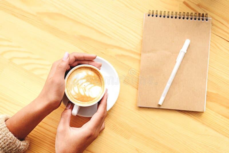 Τοπ άποψη των χεριών με το latte και το σημειωματάριο στοκ εικόνες