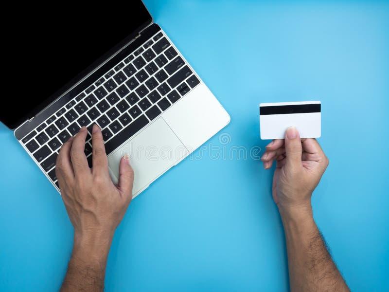 Τοπ άποψη των χεριών στο lap-top υπολογιστών και της πιστωτικής κάρτας στο μπλε υπόβαθρο Διαδίκτυο και σε απευθείας σύνδεση έννοι στοκ φωτογραφία με δικαίωμα ελεύθερης χρήσης