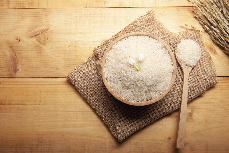 Τοπ άποψη jasmine του ρυζιού με jasmine το λουλούδι στην κορυφή σε ένα ξύλινους κύπελλο, burlap κουταλιών έναν σάκο και ένα αυτί  στοκ εικόνες με δικαίωμα ελεύθερης χρήσης