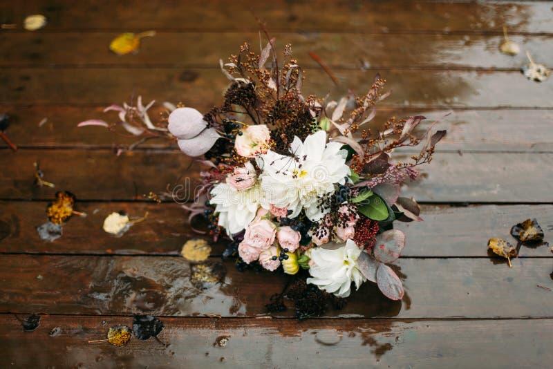 Τοπ ανθοδέσμη λουλουδιών στο ξύλινο πάτωμα μετά από τη βροχή στοκ φωτογραφία