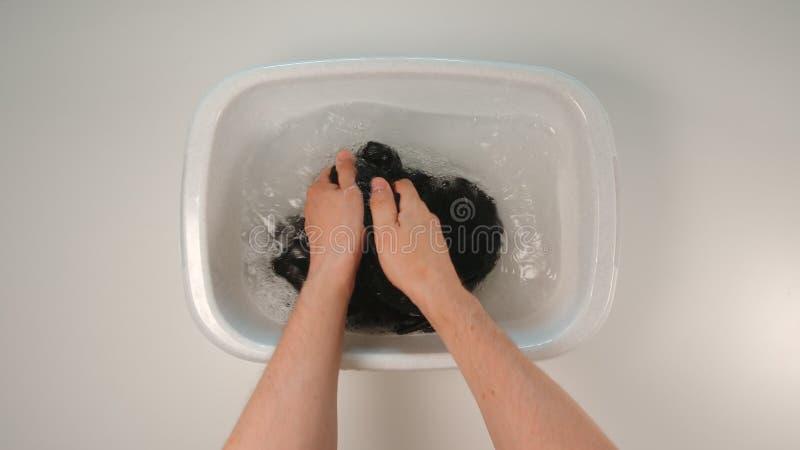 ΤΟΠ ΑΠΟΨΗ: Το νέο ενήλικο χέρι ατόμων πλένει τα ενδύματα σε μια λεκάνη στοκ εικόνες