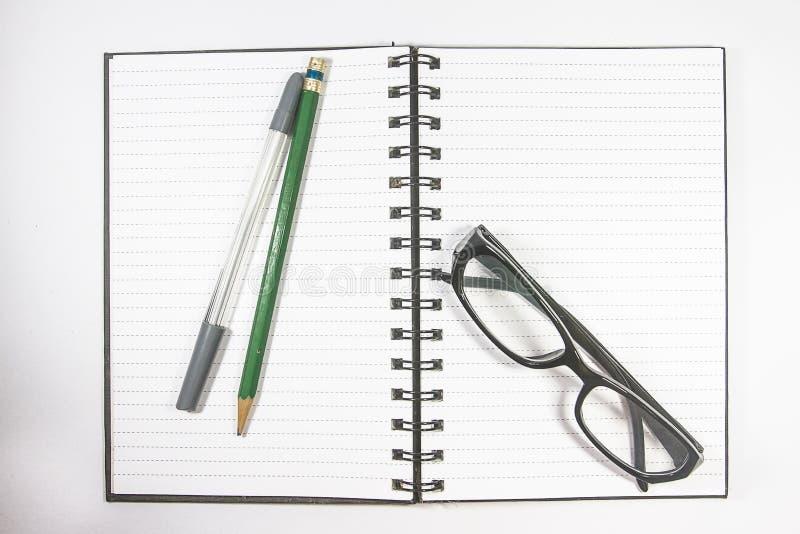 Τοπ γυαλιά ματιών άποψης με το σημειωματάριο μολυβιών, στυλών και συνδέσμων που απομονώνεται στο άσπρο υπόβαθρο στοκ φωτογραφία με δικαίωμα ελεύθερης χρήσης