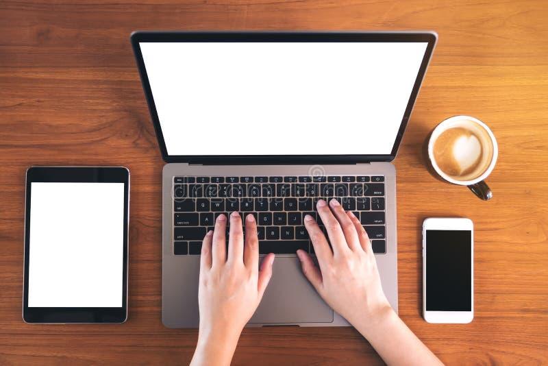 Τοπ εικόνα άποψης προτύπων των χεριών που δακτυλογραφούν στο lap-top με την κενή άσπρη οθόνη, κινητό τηλέφωνο, ταμπλέτα, φλυτζάνι στοκ εικόνα