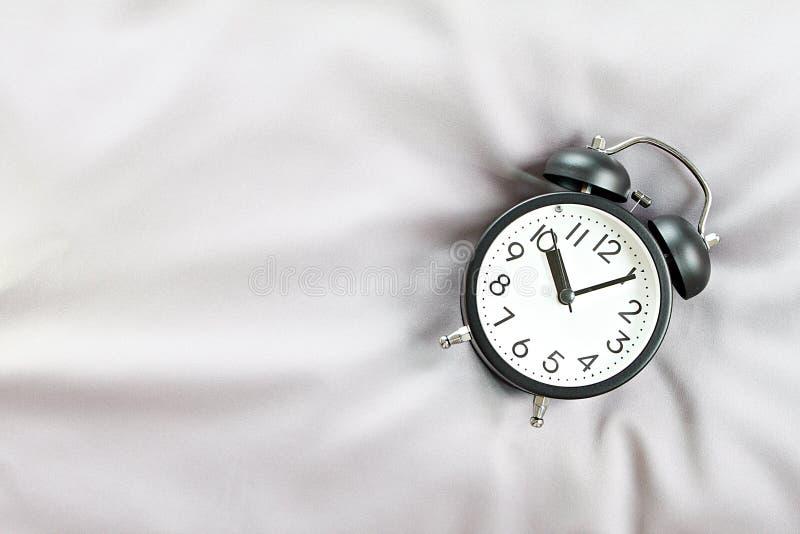 Τοπ εικόνα άποψης του μαύρου αναδρομικού ξυπνητηριού στο κρεβάτι το πρωί, έτοιμη για να προσθέσει ή τη χλεύη επάνω στοκ εικόνες με δικαίωμα ελεύθερης χρήσης