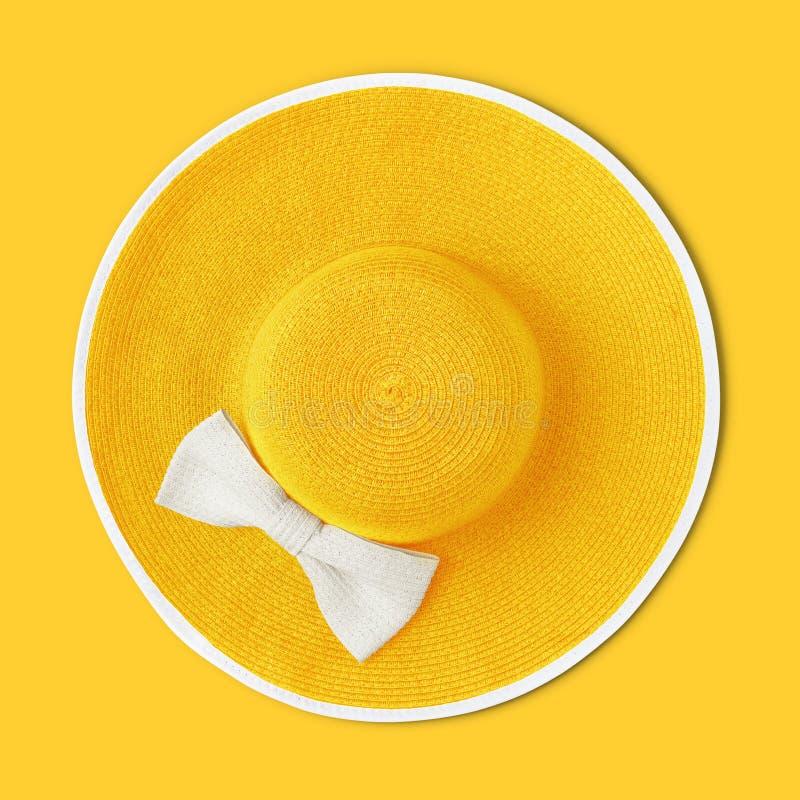 Τοπ θερινή παραλία άποψης γύρω από το κίτρινο καπέλο αχύρου με το άσπρο τόξο που απομονώνεται στο κίτρινο υπόβαθρο στοκ φωτογραφία