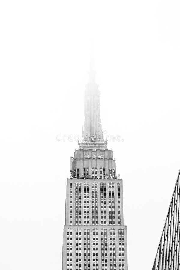 Τοπ μισό του Εmpire State Building τον πύργο που χάνεται με στην ομίχλη στοκ εικόνα